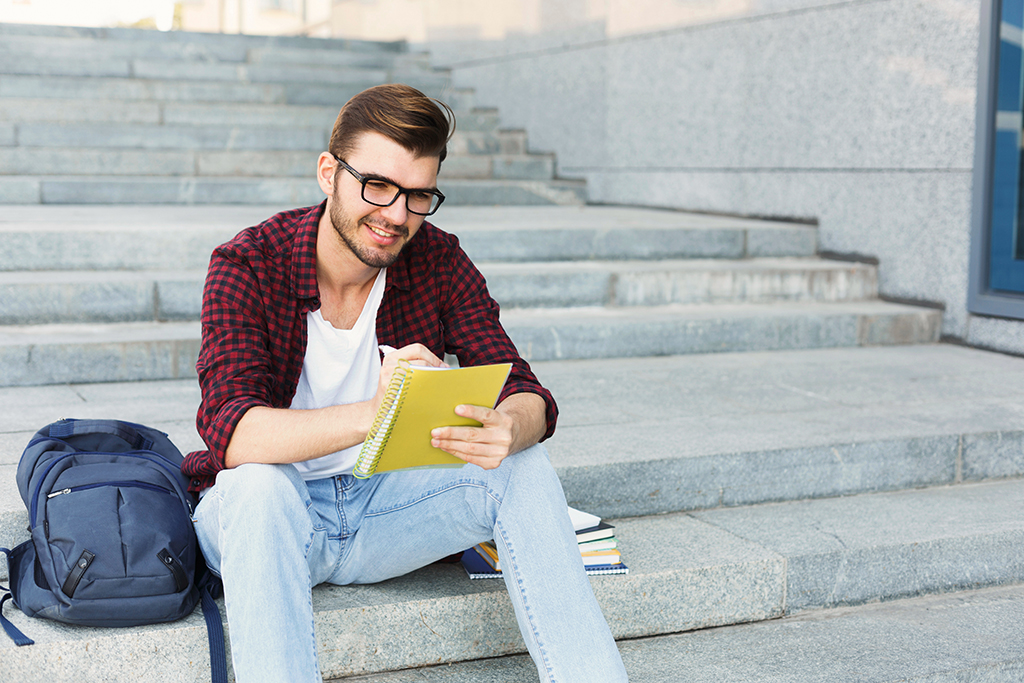 Young student sitting on stairs outdoors, making notes, preparing for exams at university or college. Education, inspiration concept, copy space